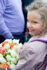 Маленькая ученица с букетом цветов смотрит в сторону и улыбается