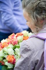 Маленькая ученица с букетом цветов роз.