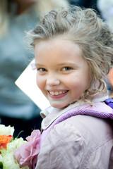 Маленькая девочка с букетом цветов оглядывается и улыбается.