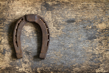Old rusty horseshoe on vintage board abstract background