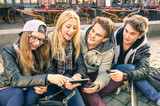 Young hipster friends having fun together with smartphones