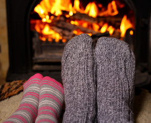 Mom and daughter warm their socked feet by the fire