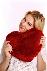Young woman hugging heart-shaped pillow.