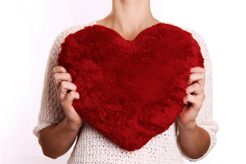 woman hugging heart-shaped pillow.