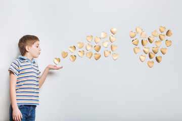Boy blowing golden hearts from hand
