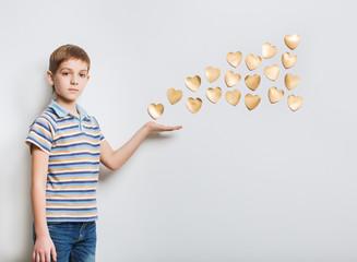 Boy holding flying golden hearts over light grey background