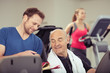 trainer und älterer kunde im gespräch im sportclub