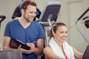trainer im fitness-studio notiert daten