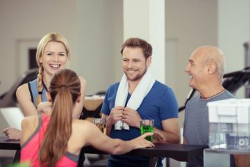 lachende gruppe nimmt ein getränk im fitness-studio
