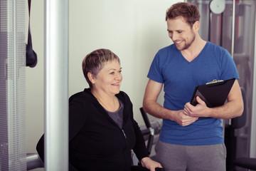 freundlicher trainer berät eine ältere frau im fitness-club