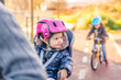 Lttle girl with helmet on head sitting in bike seat - 76989933