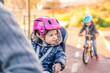 Leinwanddruck Bild - Lttle girl with helmet on head sitting in bike seat