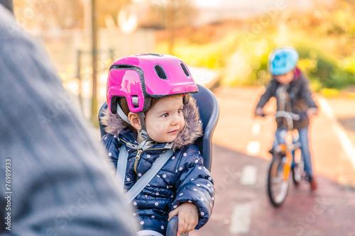 Leinwanddruck Bild Lttle girl with helmet on head sitting in bike seat