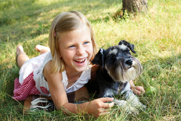 cute girl hugging her dog sitting on the grass