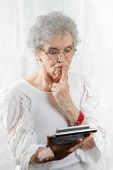 alte Frau schaut erstaunt auf Taschenrechner