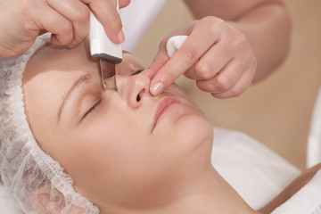 Face cleaning with ultrasonic equipment at beauty treatment