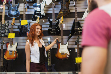 assistant showing customer guitar at music store