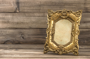 Golden baroque picture frame on wooden background