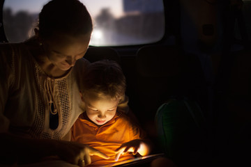 Mother and son with pad during car travel at night