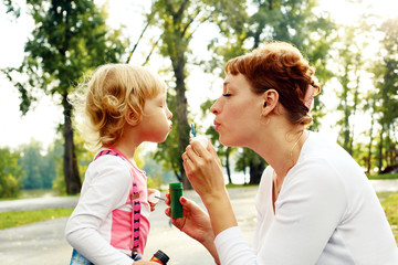 happy mother and her daughter blowing soap bubbles on a warm sum