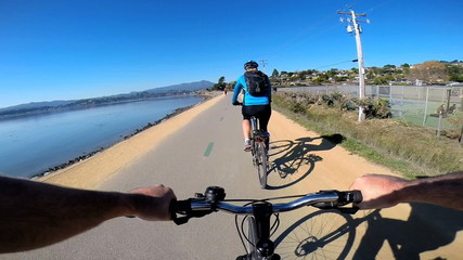 POV bike riding couple rural track lakeside lifestyle activity, USA