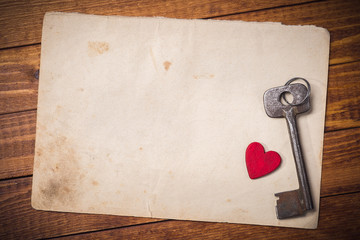 Old key and wooden heart on a background of old paper with space