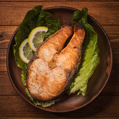 Baked trout steak in pottery with salad and slices of lemon, top