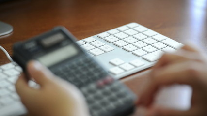 An accountant enters expenses on a calculator and computer