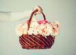 man's hand holding basket full of flowers