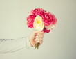 man's hand giving bouquet of flowers