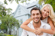 canvas print picture - smiling couple hugging over house background