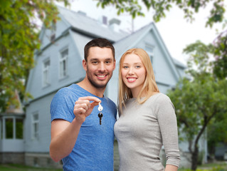 smiling couple showing key over house background