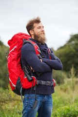 smiling man with backpack and binocular outdoors