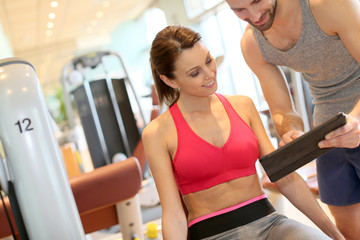 Fitness girl with coach setting up program
