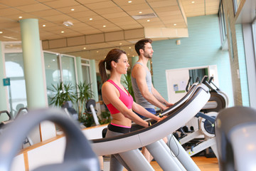Couple in fitness center working out on cardio machine