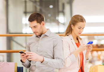 couple with smartphones and shopping bags in mall