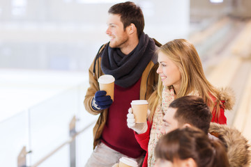 happy friends with coffee cups on skating rink