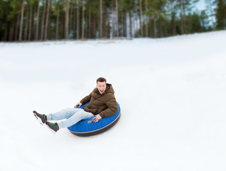 happy young man sliding down on snow tube
