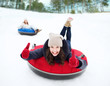 canvas print picture - group of happy friends sliding down on snow tubes