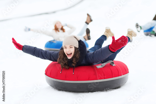 group of happy friends sliding down on snow tubes - 77001120