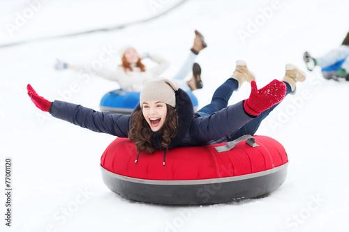 Leinwandbild Motiv group of happy friends sliding down on snow tubes