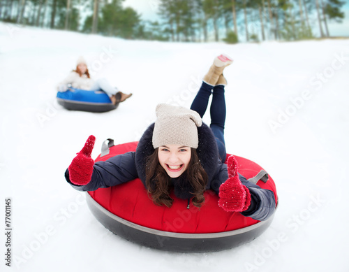 canvas print picture group of happy friends sliding down on snow tubes