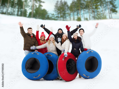 group of smiling friends with snow tubes - 77001382