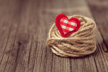 Red valentine's day heart in nest on wooden background with retr