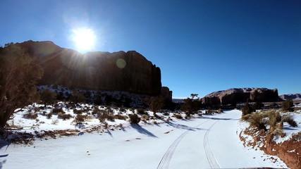 POV vehicle driving road Monument Valley winter snow blue sky Arizona USA