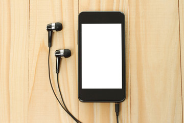 Smart phone with headphones on wooden background.