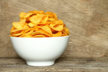 Potato chips bowl on a wooden background .