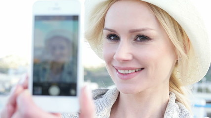 blonde woman takes selfie with her smartphone