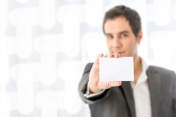 Businessman holding up a blank white card