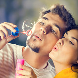 Couple blowing bubbles, outdoor